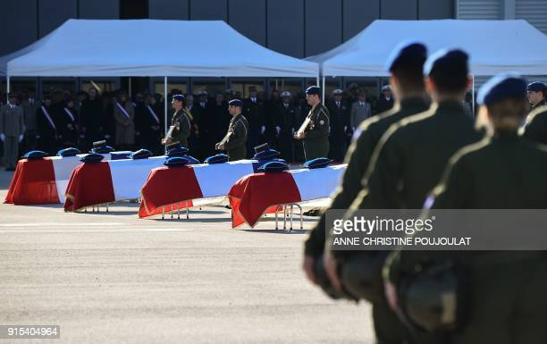Military men three holding a photo of some of the victims stand at attention by caskets during a national tribute ceremony to five helicopter pilot...