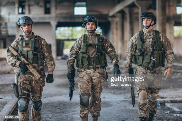 military men walking in abandoned warehouse - task force stock pictures, royalty-free photos & images