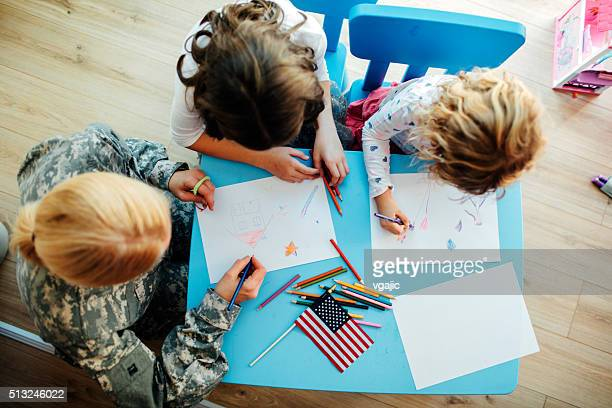 Military Mom Coloring With Her Kids, top view.