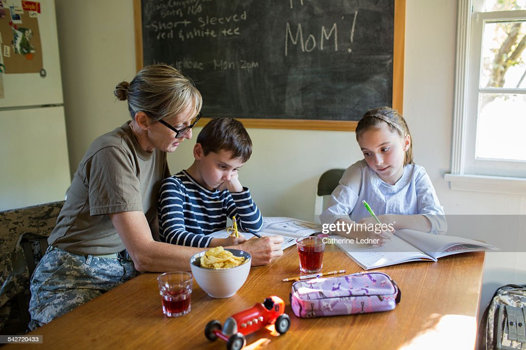 Military Mom helping her Children with Homework : Stock-Foto