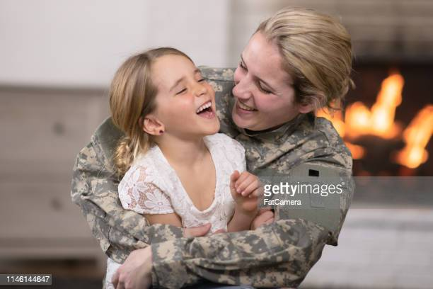 military mom hugging her daughter - army soldier stock pictures, royalty-free photos & images