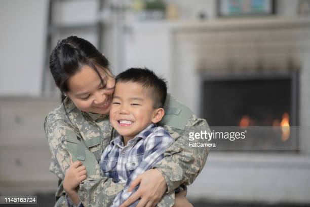 military mom hugging her son - philippines stock pictures, royalty-free photos & images