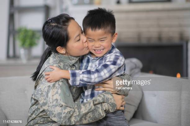 military mom hugging her son - canadian politics stock pictures, royalty-free photos & images
