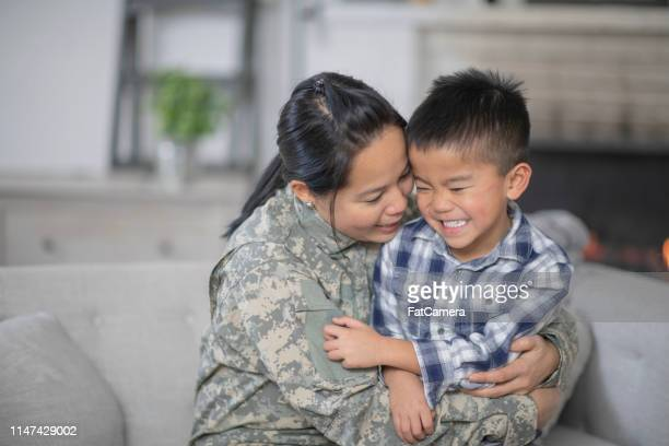 military mom hugging her son - filipino family reunion stock pictures, royalty-free photos & images