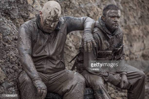 military mud run portrait of 3 soldiers - trench warfare stock photos and pictures