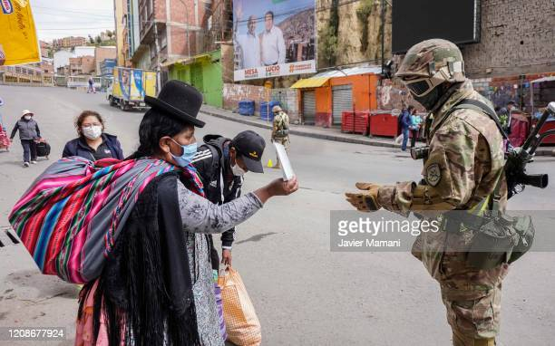 Military officer asks a woman for his identity card at a checkpoint on March 30, 2020 in La Paz, Bolivia. Bolivia has established a blockade to...