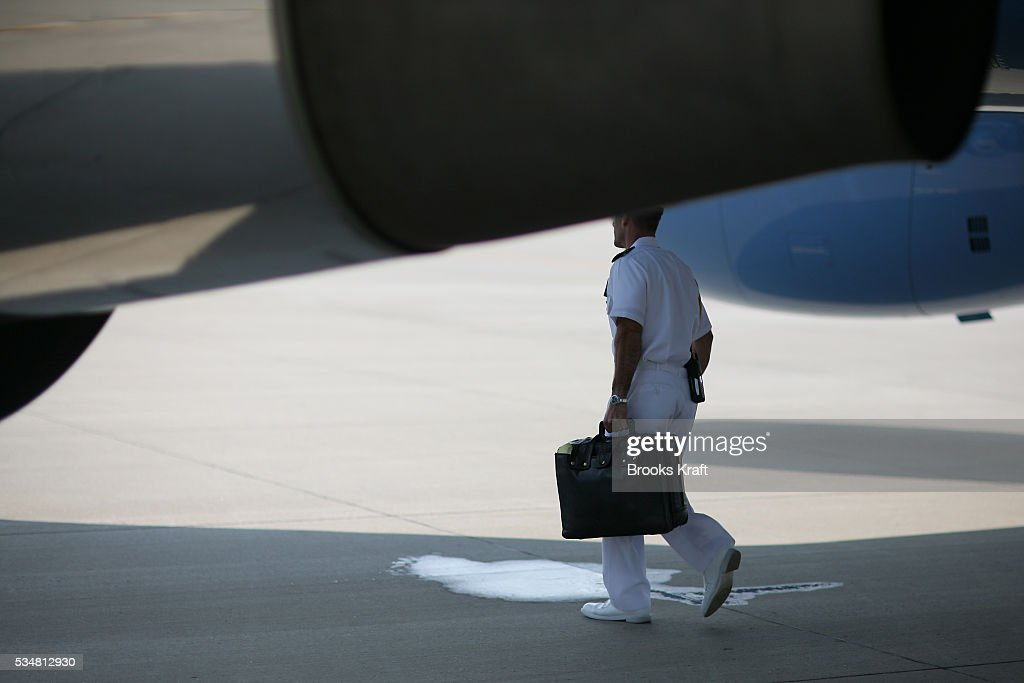 A military officer carries the 'Football' under Air Force One at Andrews Air Force Base, July 26, 2006. The Football is a secure package that contains the necessary Gold Codes, or nuclear launch codes, the president's Decision Book, which details nuclear strike options available to the president, and a secure SATCOM radio and handset. It follows the president wherever he travels and is never more that a few steps from his side. The military officer who carries the Football undergoes the nation's most rigorous security background check.