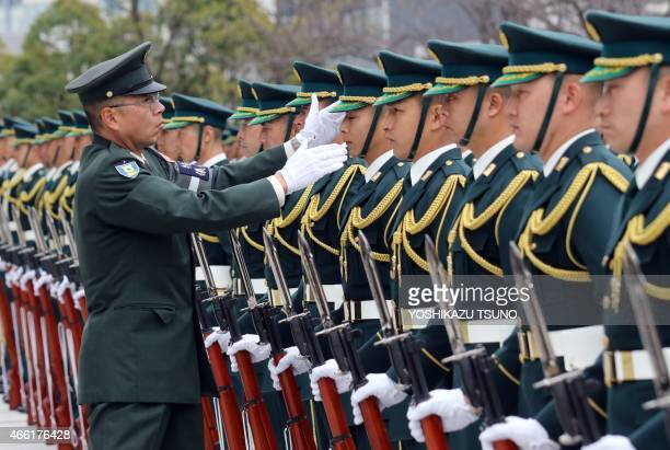 Military officer checks the appearance of Japanese honour guards before a welcoming ceremony for French Defence Minister Jean-Yves Le Drian at the...