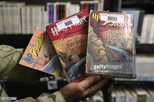 A military officer displays copies of Harry Potter books in Arabic and English at in the library of the Gitmo maximum security detention center on...