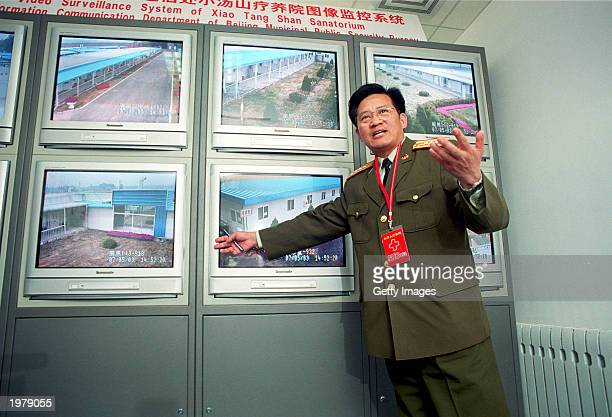 A military officer explains the surveillance system of the newly built 1000 bed SARS hospital to journalists on May 7 2003 in Xiaotangshan China is...