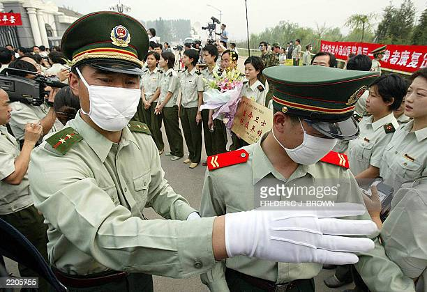 A military officer gestures to keep back journalists covering the release of Severe Acute Respiratory Syndrome patients from the Xiaotangshan SARS...