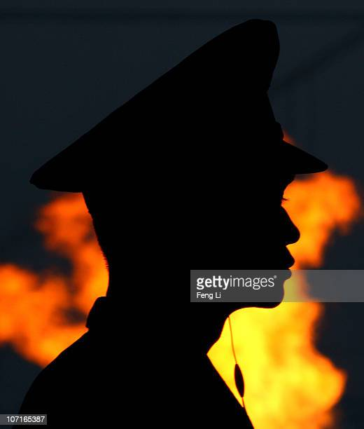 A military officer looks on from his position as the flame burns behind him during the Closing Ceremony at Haixinsha Square on day fifteen of the...