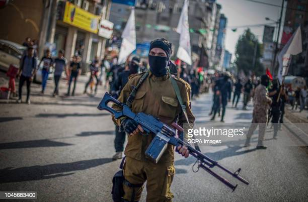 A military officer seen holding a gun during the march Members of the Palestinian AlQuds Brigades the military wing of the Islamic Jihad group march...