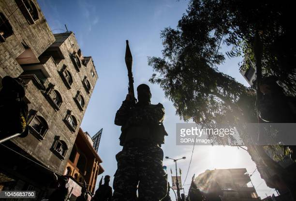 A military officer seen holding a weapon during the march Members of the Palestinian AlQuds Brigades the military wing of the Islamic Jihad group...