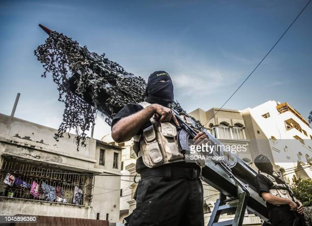 A military officer seen standing in front of a Gazan local made rocket during the parade Members of the Palestinian AlQuds Brigades the military wing...