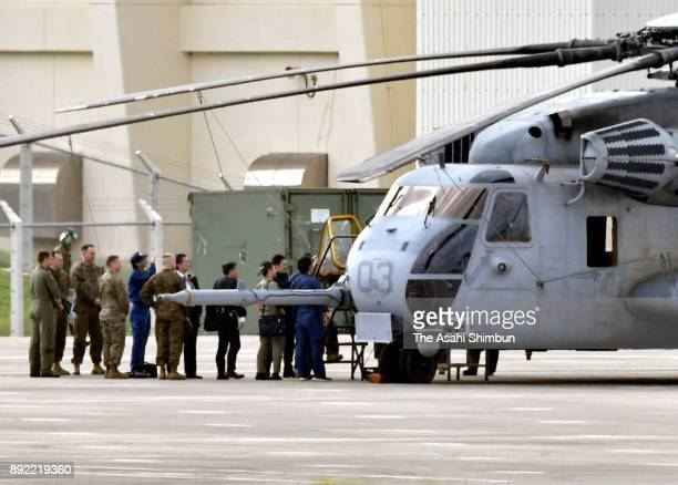 US military officers and Okinawa Prefecture Police officers investigate a CH53E helicopter at US Marine Corps Air Station Futenma on December 14 2017...