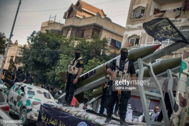 Military officers are seen on top of the truck holding guns during the march Members of the Palestinian AlQuds Brigades the military wing of the...