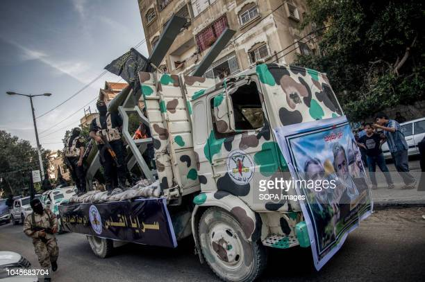 Military officers are seen on top of the truck holding weapons during the march Members of the Palestinian AlQuds Brigades the military wing of the...