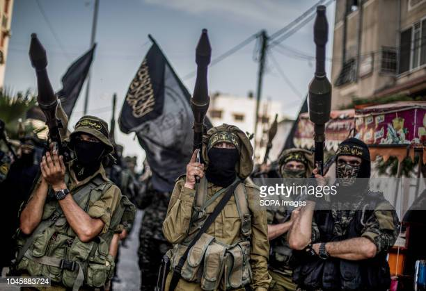 Military officers are seen standing holding weapons during the march. Members of the Palestinian Al-Quds Brigades, the military wing of the Islamic...