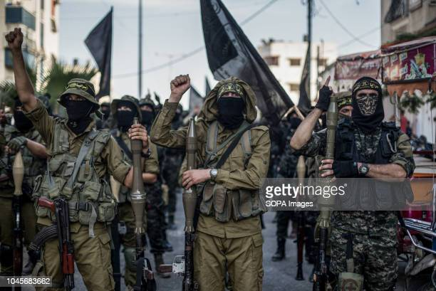Military officers are seen standing rising up their fists while holding weapons during the march Members of the Palestinian AlQuds Brigades the...