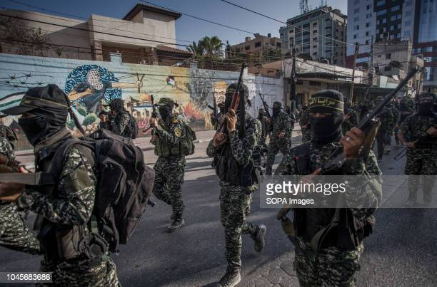 Military officers are seen walking holding guns during the march Members of the Palestinian AlQuds Brigades the military wing of the Islamic Jihad...