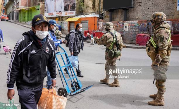 Military officers ask people for their identity card at a checkpoint on March 30, 2020 in La Paz, Bolivia. Bolivia has established a blockade to...
