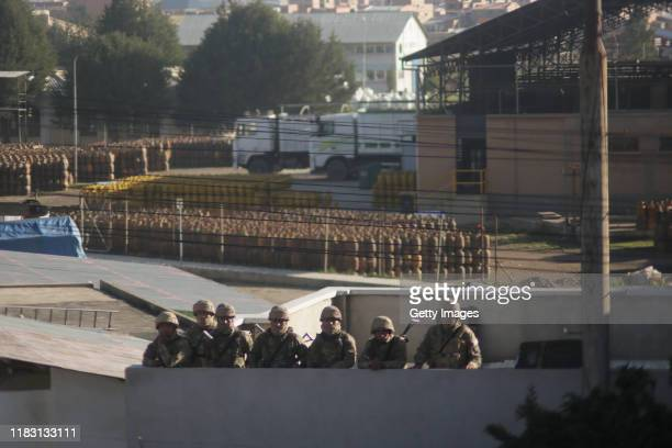 Military officers look on from inside the Yacimientos Petroliferos Fiscales Bolivianos oil refinery during a blockade as part of a protest against...