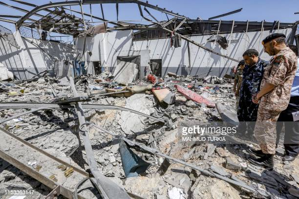 Military officers of the Libyan Government of National Accord inspect damage and debris at a migrant detention centre used by the GNA in the capital...
