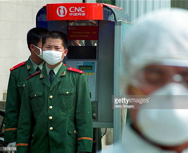 Military officers wearing facial masks and gloves waits while on duty at the newly built 1000 bed Xiaotangshan hospital on May 7 2003 in Beijing...