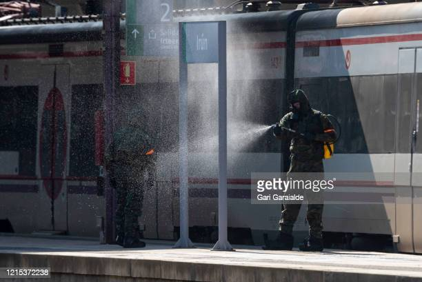 Military officers wearing protective suits and masks carry out a general disinfection of Irun train station on March 28 2020 in Irun Spain Spain...
