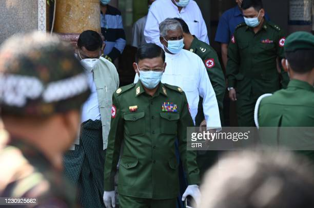 Military official accompanied by soldiers leaves a Hindu temple in Yangon on February 2 as Myanmar's generals appeared in firm control a day after a...