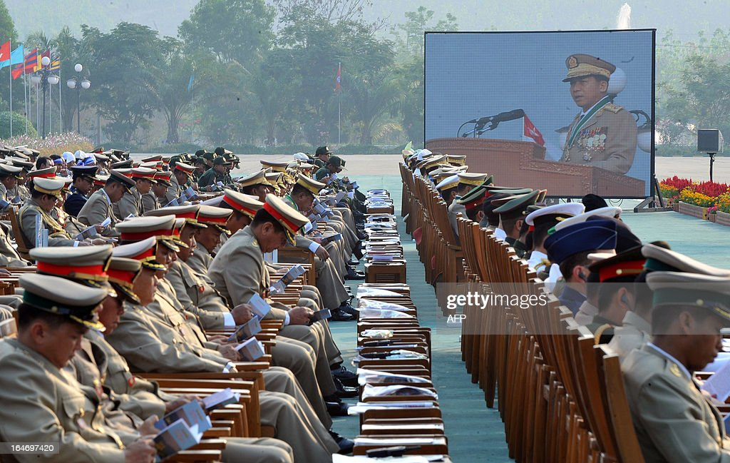 Military officials listen to a speech by Commander in Chief Min Aung Hlaing (screen R) during a ceremony marking Myanmar's 68th Armed Forces Day at a parade ground in Naypyidaw on March 27, 2013. Opposition leader Aung San Suu Kyi attended Myanmar's Armed Forces Day for the first time. AFP PHOTO / Ye Aung THU