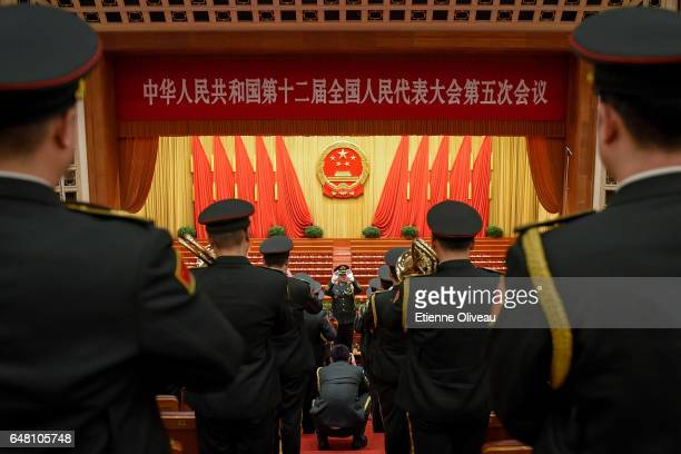 Military orchestra conductor leads the band as a military photographer takes his portrait after the opening session of the National People's Congress...