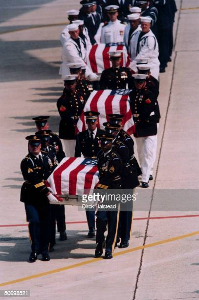 Military pallbearers carrying flagdraped coffins of Americans killed in terrorist bombing of US Embassy in Nairobi Kenya arriving at Andrews AFB for...