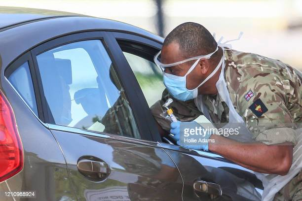 A military person takes a swab at a drivein COVID19 testing centre at Chessington World of Adventures Resort theme park on April 24 2020 in...