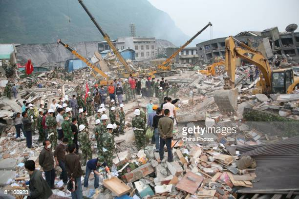Military personel work on the debris of collapsed houses in search of victims in the Ronghua Township May 15, 2008 in the outskirts of Shifang, one...
