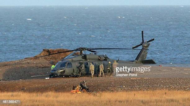 Military personnel and emergency services attend the scene on the coast after an US Air Force helicopter crashed on marshland on January 8 2014 in...