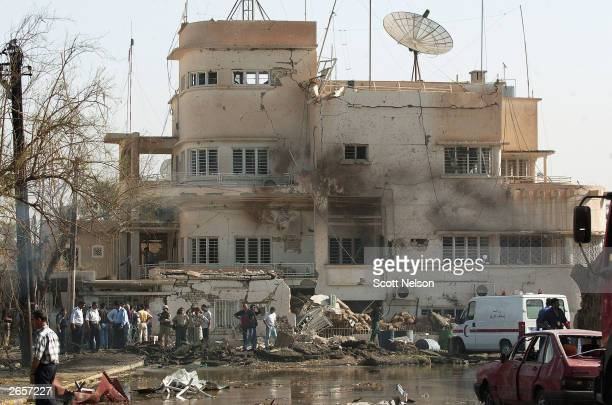 S military personnel and Iraqi security forces investigate the scene of a massive car bomb attack on the headquarters of the International Committee...