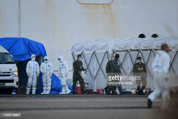 Military personnel and medical staff clad in protective gear are seen at work near the quarantined Diamond Princess cruise ship at Daikoku Pier...