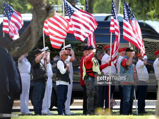 Military personnel and veterans salute as the funeral procession for Sen John McCain arrives at the Arizona State Capitol Rotunda where McCain's body...