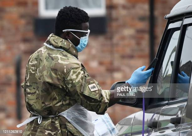 Military personnel assist at a drivein testing facility for the novel coronavirus COVID19 in Macclesfield northwest England on April 29 2020