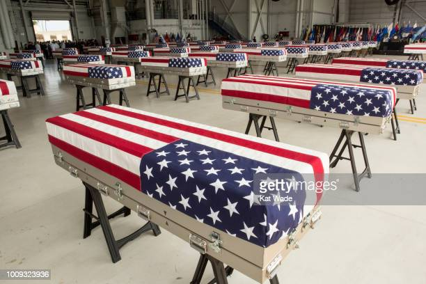 Military personnel bring in the presumed remains of US soldiers in 55 caskets draped with American flags into Hanger 19 Joint base Pearl Harbor...