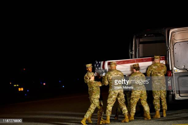 Military personnel carry a transfer case for fallen service member US Navy Ensign Joshua Kaleb Watson during a dignified transfer at Dover Air Force...