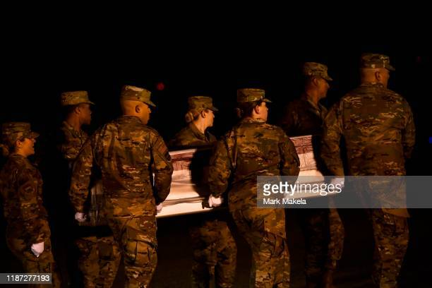 Military personnel carry a transfer case for fallen service member US Navy Seaman Apprentice Cameron S Walters during a dignified transfer at Dover...
