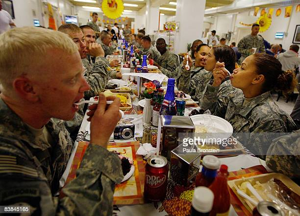 US military personnel enjoy a special meal in celebration of America's annual Thanksgiving Day tradition in the dining hall at the US military...