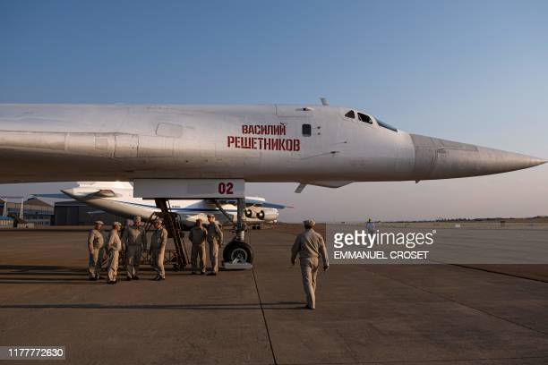 Military personnel gather under a Russian Air Force Tupolev Tu160 Blackjack a supersonic variablesweep wing heavy strategic bomber is parked on the...