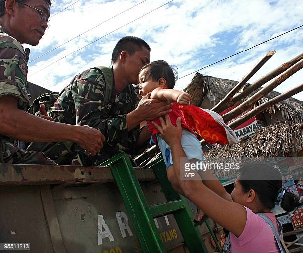 Military personnel help a mother with her child during a forced evacuation of residents living at the foot of the Mayon volcano in Bonga near the...
