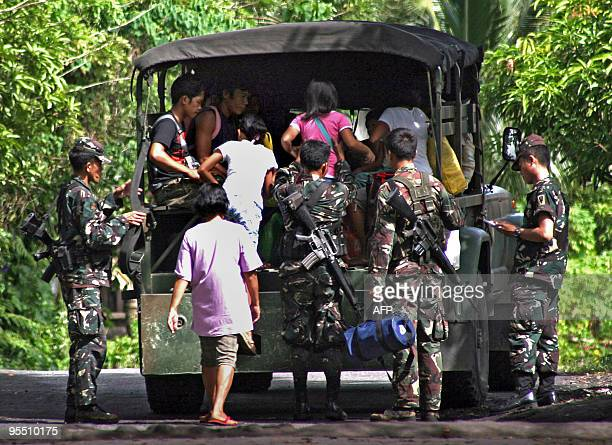Military personnel help residents board their vehicle during a forced evacuation for people living at the foot of the Mayon volcano in Bonga near the...