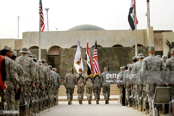 S Military personnel holding the US flag Iraq flag and the US Forces Iraq colors march during a casing ceremony where the United States Forces Iraq...