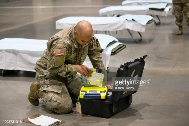 Military personnel including Brandon Lawrence from Tacoma Washington checking the battery on an automated external defibrillator set up the 627th...